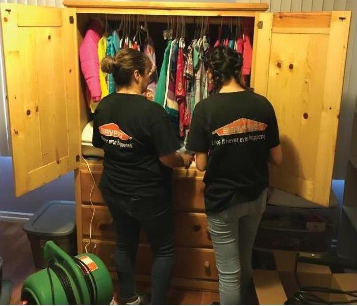 2 girls in front of a closet