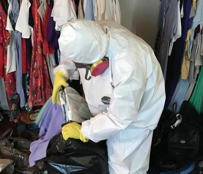 man in white PPE putting clothes in bag