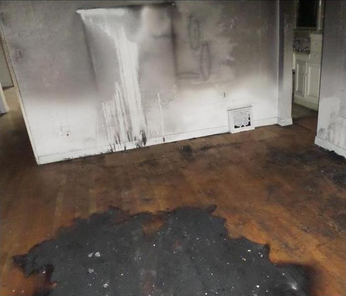 hardwood floor and white wall with black soot and damage