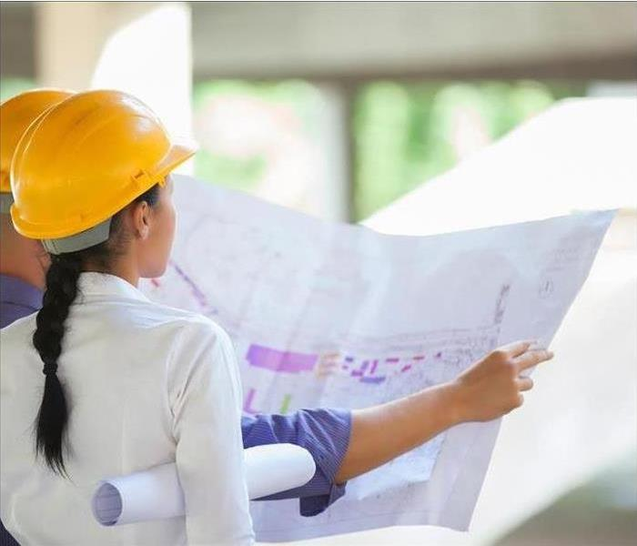 a picture of a woman looking at construction plans